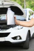 Motor oil in hand — Stock Photo