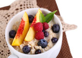 Oatmeal in cup with berries on napkins isolated on white — Stock Photo