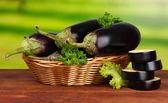 Berinjelas frescas na cesta de vime na mesa sobre fundo de madeira — Foto Stock