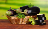 Fresh eggplants in wicker basket on table on wooden background — 图库照片