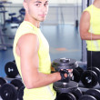 Guy with dumbbells in gym — Stock fotografie