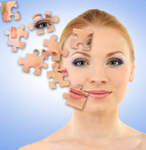 Beautiful girl with parts of skin on puzzles on blue background — Stock Photo