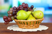 Pears and grape in wicker basket, on bright background — Stock Photo
