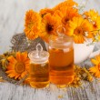 Medicine bottles and calendula flowers on wooden background — Stock Photo #30871953