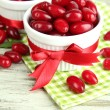 Fresh cornel berries in white cups on wooden table — Stock Photo