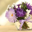 Beautiful bouquet of bright flowers in glass vase, on wooden table, on bright background — Stock Photo #30873355