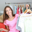 Stock Photo: Beautiful girl with lots clothes in room background