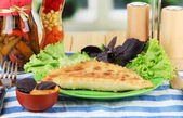 Tasty chebureks with fresh herbs on plate,on wooden table, on bright background — Stock Photo