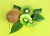 Ripe kiwi on green wooden table close-up — Stock Photo
