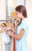 красивая девушка выбирает одежду на вешалках на фоне номер — Стоковое фото