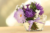 Beautiful bouquet of bright flowers in glass vase, on wooden table, on bright background — Stock Photo