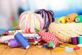 Wicker basket with accessories for needlework on wooden table, on bright background — Stock Photo