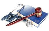 Conceito de direito medicina. martelo e estetoscópio no livro isolado no branco — Foto Stock