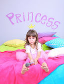 Little girl sings on bed in room on grey wall background — Stock Photo