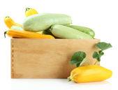 Syrové žluté a zelené cukety v dřevěné bedně, izolované na bílém — Stock fotografie