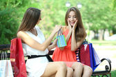 Two beautiful young woman with shopping bags in park — Foto de Stock