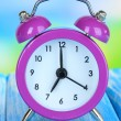 Stock Photo: Alarm clock on table on blue background