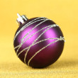 Christmas ball on yellow background — Stock Photo