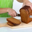 Cutting bread on wooden board isolated on white — Stock Photo