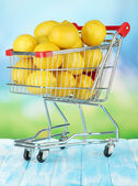 Ripe lemons in trolley on table on bright background — Stock Photo