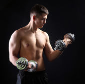 Handsome young muscular sportsman execute exercise with dumbbells on dark background — Stock Photo