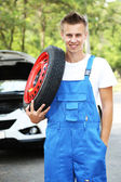 Auto mechanic with tire on his shoulder — Stock Photo