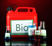 Bio fuels in canister and vials on red background — Stockfoto