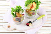 Fruit salad in glasses, on wooden background — Stock Photo