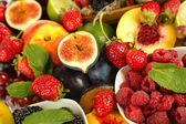 Assortment of juicy fruits and berries background — Stock Photo