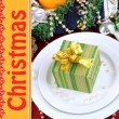 Small Christmas gift on plate on serving Christmas table close-up — Stock Photo