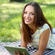 Beautiful young girl with tablet in park — Stock Photo