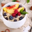 Oatmeal in cup with berries on napkins on wooden table — Stock Photo
