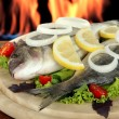 Dorado fish on table on fire background — Stock Photo