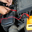Auto mechanic uses multimeter voltmeter to check voltage level in car battery — Stock Photo #30934235
