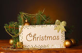 Christmas balls and fir-tree on wooden table on brown background — Stock Photo
