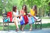 Three beautiful young woman with shopping bags in park — Fotografia Stock