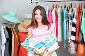 Beautiful girl with lots clothes in room background — Stockfoto