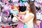 Beautiful young woman in shop with underwear — Stock Photo