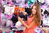 Hermosa joven en tienda con ropa interior — Foto de Stock