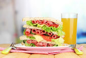 Huge sandwich on wooden table, on bright background — Stock Photo