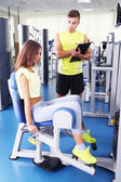 Girl and trainer engaged in simulator in gym — Stock Photo