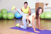 Girl and trainer engaged in fitness room — Stock Photo