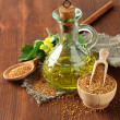 Jar of mustard oil and seeds with mustard flower on wooden background — Stock Photo