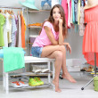 Stock Photo: Beautiful girl thinking what to dress in walk-in closet