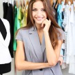 Beautiful young stylist near rack with hangers — Foto Stock #31014079