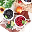 Raspberries and blackberry in small bowls on napkin on wooden table — Stock Photo