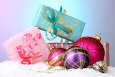 Beautiful Christmas balls and gifts on snow on bright background — Стоковое фото