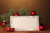 Blank postcard, Christmas balls and fir-tree on wooden table on brown background — Stock Photo