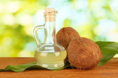Decanter with coconut oil and coconuts on green background — Stock Photo