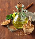 Jar of mustard oil and seeds with mustard flower on wooden background — Stockfoto